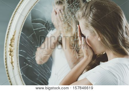 Woman with mental problems covering her face reflected in mirror