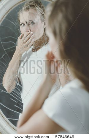 Broken mirror reflection of depressed woman covering her mouth
