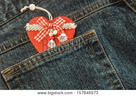 Jeans texture with pocket and handmade wooden red Christmas heart with ribbon and bells.