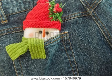 Snowman tucked into denim trouser pocket. Christmas and New Year concept.