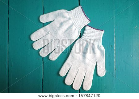Working gloves on wooden background. Cloth gloves on a wooden texture