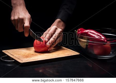 For a dish. Close up of young chef mans hands chopping tomato while cooking and preparing vegetables for salad in restaurant.