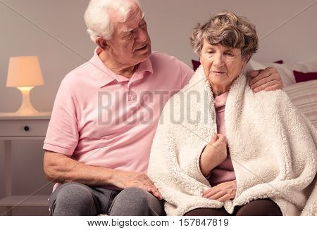 Caring Grandfather And Grandmother With Blanket