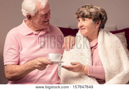 Elderly Man Giving Tea Sick Wife