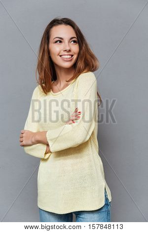 Portrait of a cheerful young woman in sweater standing with arms folded and looking away isolated on the gray background