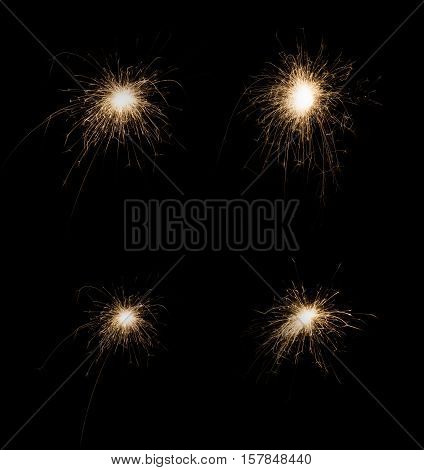 New year party burning sparklers on black background. Glowing holiday sparkling hand fireworks, shining fire flame. Christmas light.
