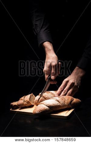 French taste. Close up of male chefs hands chopping the baguette on a black background while cooking and working in restaurant.