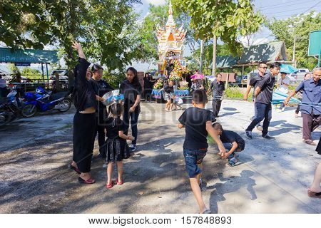 CHIANG RAI THAILAND - NOVEMBER 19 : unidentified Thai people finding coins on the ground in thai traditional funeral on November 19 2016 in Chiang rai Thailand