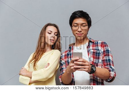 Jealous girlfriend watching his boyfriend texting on the phone isolated on gray background