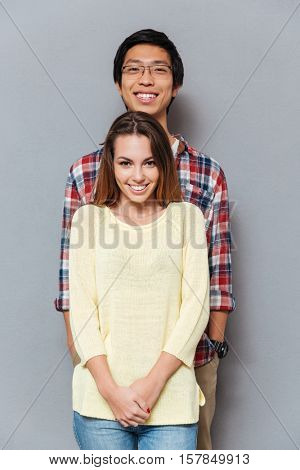 Pportrait of a smiling cheerful interracial couple standing together and looking at camera isolated on the gray background