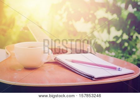 Acoustic guitars with a notebook and cup of coffee on table, music relax time in home garden