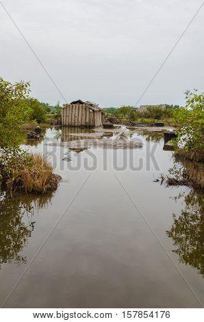 Simple reed mat homes of poor fishermen in wetlands of Benin, Africa.