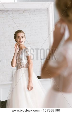 The last preparation. Pleasant charming young bride looking in the mirror while standing in the white room and expressing tenderness