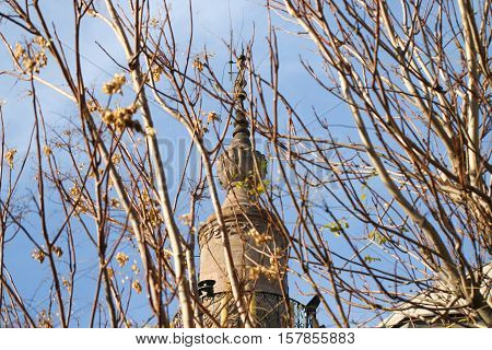The top of the minaret of the mosque against the blue sky behind the trees.