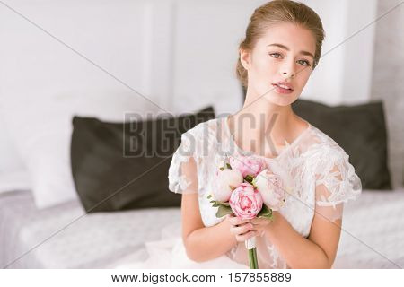 Full of excitement.Charming delighted young bride sitting on the bed in white colored room while holding the bouquet and expressing tenderness