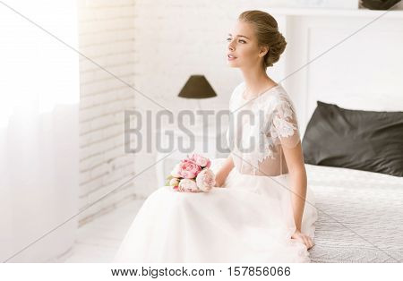 Full of expectation . Thoughtful delighted young bride sitting on the bed in white colored room while holding the bouquet and expressing tenderness and expectation