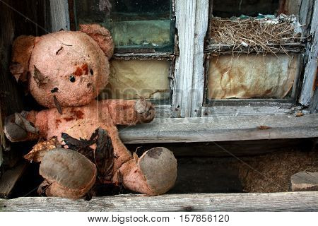 Sad child doll - old toy bear in the ruins. Neglect concept.