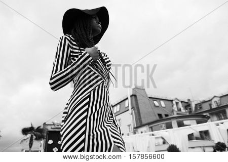 Black and white photo of charming, touching, tender, beautiful african woman wearing dress in stripes and hat on her head. Model staying on the teritory of vip hotel with modern interior.
