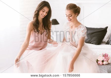 Fitting of the wedding dress. Cheerful smiling young bride and bridesmaid sitting in the white room while being in interaction with each other and looking at the wedding dress