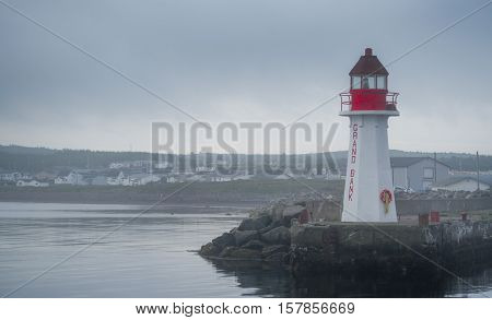 Red & white lighthouse in quiet Grand Bank, Newfoundland.  Gray, overcast morning on Atlantic shoreline.  A lone lighthouse atop an outcropping of rock at the end of a pier. poster
