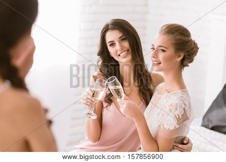 Bridesmaids and bride having fun. Delighted smiling young bride and bridesmaid sitting in the white room while drinking champagne and posing to the camera