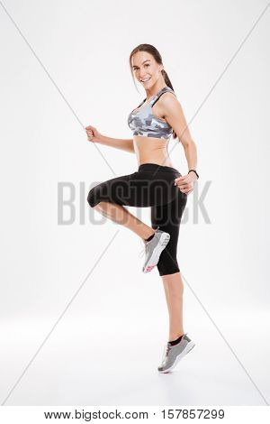 Full length aerobic woman dancing in studio. stands sideways. looking at camera