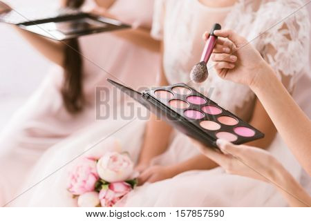 Great palette of blusher. Pleasant good looking young bridesmaids sitting in the white bedroom while helping the bride to get ready and holding the palette of blusher