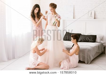 The last moment of the maidhood. Amused smiling young bridesmaids sitting in the white bedroom while helping the bride to get ready and expressing joy