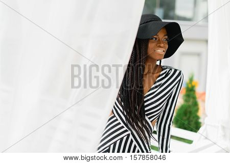 Attractive woman in black hat and striped dress. White light sunblind around. Model sitting on the fence and smiling.