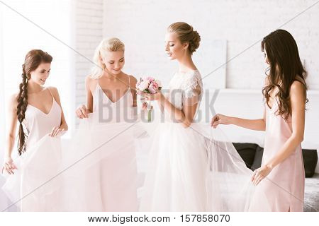 Look at you. Excited smiling young bridesmaids standing in the white bedroom while helping the bride to get ready and expressing excitement