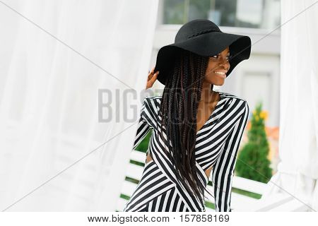 Attractive, adorable woman in black hat and striped dress. White light sunblind around. Model sitting on the fence and smiling. Luxury hotel.
