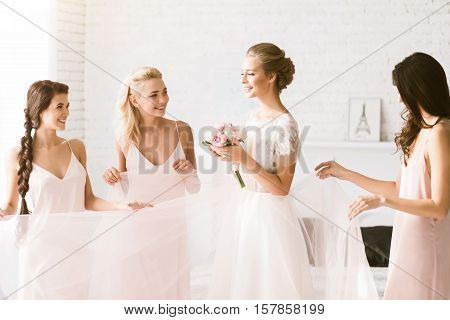 We happy together. Delighted smiling young bridesmaids standing in the white bedroom while helping the bride to get ready and expressing happiness