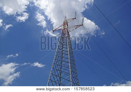 High Voltage Power Lines Intersect At A Large Metal Utility Pole In Maine Against  Blue Sky.