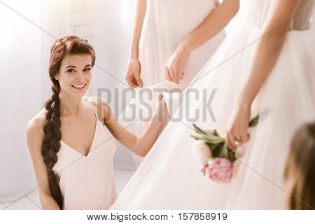 Full of happiness. Cheerful smiling young bridesmaid sitting in the white bedroom while helping with other bridesmaid the bride to get ready and expressing happiness