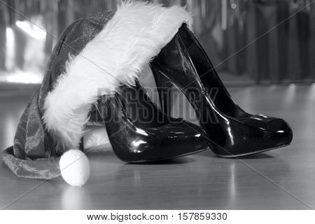 Black high heeled shoes next to Santa Claus hat