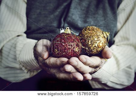 closeup of an old caucasian man with some christmas balls in his hands, with a retro effect