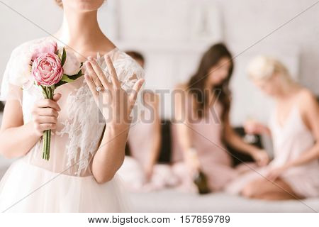 Engagement ring. Pleasant shy young bride standing in the white colored bedroom while showing her engagement ring and her bridesmaids having fun in the background