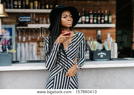 Pretty african woman in bar with red cocktail in her hand. Model put her another hand on her hat. Pretty woman in striped long dress. Wall full of bottles of alcohol on it. Ice cocktails. Margarita.