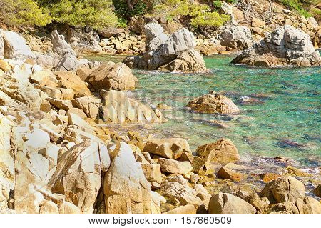 Beautiful natural rock near of Tossa de Mar Costa Brava Spain. Bay and crystal clear water of Mediterranean Sea. Amazing blue green sea and sunny day.