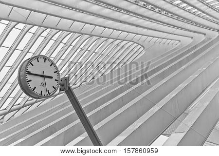 LIEGE BELGIUM - December 2014: Abstract view on the roof with station clock of the Liege-Guillemins railway station designed by Santiago Calatrava. Black and white photograph