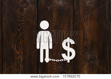 Paper man chained to dollar sign, money or business concept, abstract conceptual image