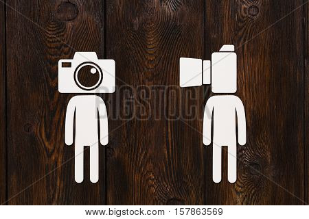Paper men with photo camera instead of head, photograper or cameraman concept, abstract conceptual image