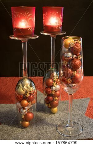 3 champagne glasses filled with colorful Christmas balls on a gray star-shaped coasters. 2 of the 3 glasses of sparkling wine are turned around and carry 2 red tea light holder with burning tea lights.