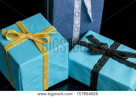 Three presents of different sizes wrapped in blue and turquoise textured paper tied with lace and velvet ribbons on black closeup from high angle