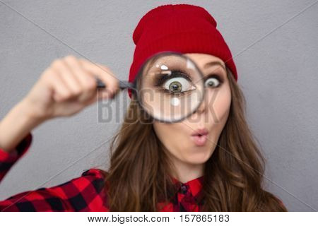 Portrait of a funny young woman looking at the camera through magnifying glass over gray background