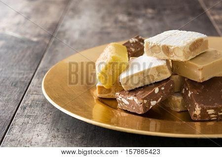 Christmas nougat on a golden plate on wooden background