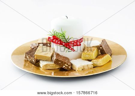 Christmas nougat and white candle on a golden plate isolated