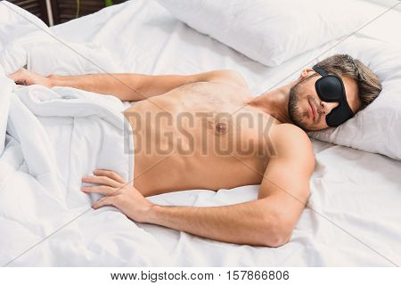 Calm young man is sleeping in bed with relaxation. His eyes are covered by eyewear