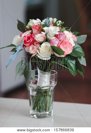 beautiful bridal bouquet standing in a glass on a wooden table wedding bouquet of roses freesias and carnations