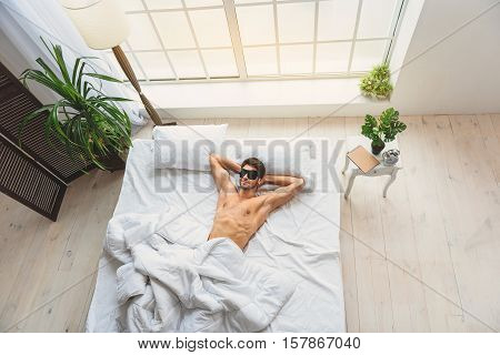 Top view of young man napping in bedroom. He is lying with relaxation and smiling